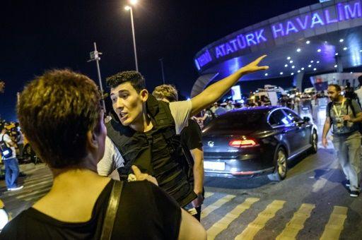 Un policier turc à l'aéroport Ataturk d'Istanbul s'adresse aux passagers après la triple attaque-suicide, le 28 juin 2016 © OZAN KOSE AFP