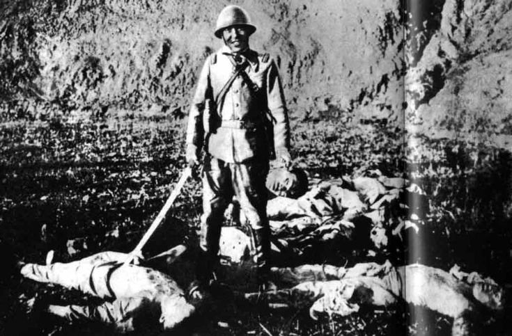 Japanese soldier holding the severed head of a Chinese civilian, Nanjing, China, Dec 1937-Jan 1938