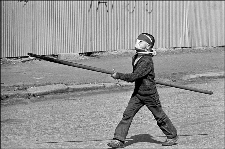 A small boy prepares to take on the British army with a home-made lance in Belfast, 1981, by Ian Berry