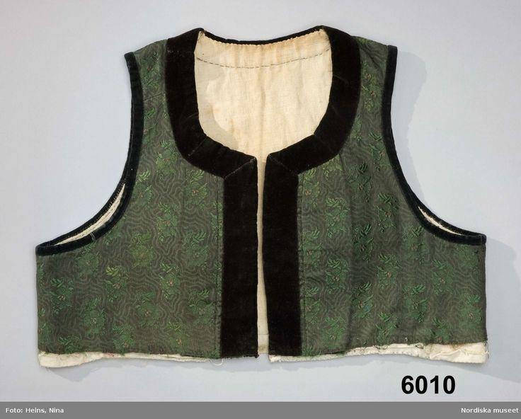 Livstycke som suttit ihop med kjol, av halvsiden, botten med vattrat mönster i svart och mörkgrönt bomull/siden med invävda spridda blommor i grönt silke. 2 framstycken, 2 sidstycken och 1 ryggstycke som slutar i spets mitt bak. Halsringning och framkanter med 3,5 cm breda svarta kanter av bomullssammet, kring ärmhålen 0,8 cm breda sammetskantningar, raka framkanter med  6 par hakar och hyskor av mässing. Foder av blekt linnelärft. Nederkanten ofållad,  i den öppna underkanten ser man att…