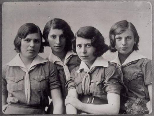 Four Jewish teenage girls who are members of the Hashomer Hatzair Zionist youth movement in Eisiskes, pose in their uniforms. All were killed by Germans during the September 1941 mass shooting action in Eisiskes