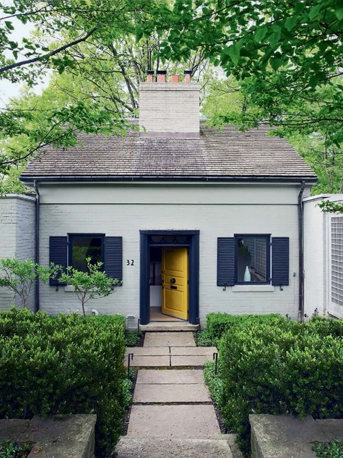 Painted brick cottage home exterior with black shutters for Front door yellow house
