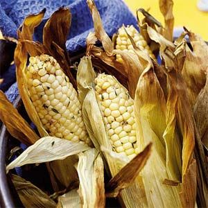 Smoking ears of corn, in the husks, over wood chips for 30 minutes creates an amazingly rich, smoky flavor. After the corn is smoked, top it with thyme butter for a fresh herb note.