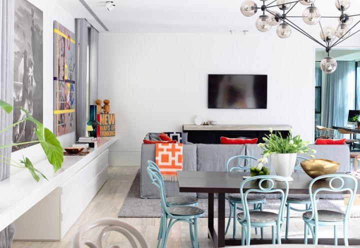 Il tavolo in legno scuro è accompagnato da sedie in legno curvato color azzurro cielo. Sopra ad essi il Modo Chandelier disegnato da Jason Miller per Roll and Hill
