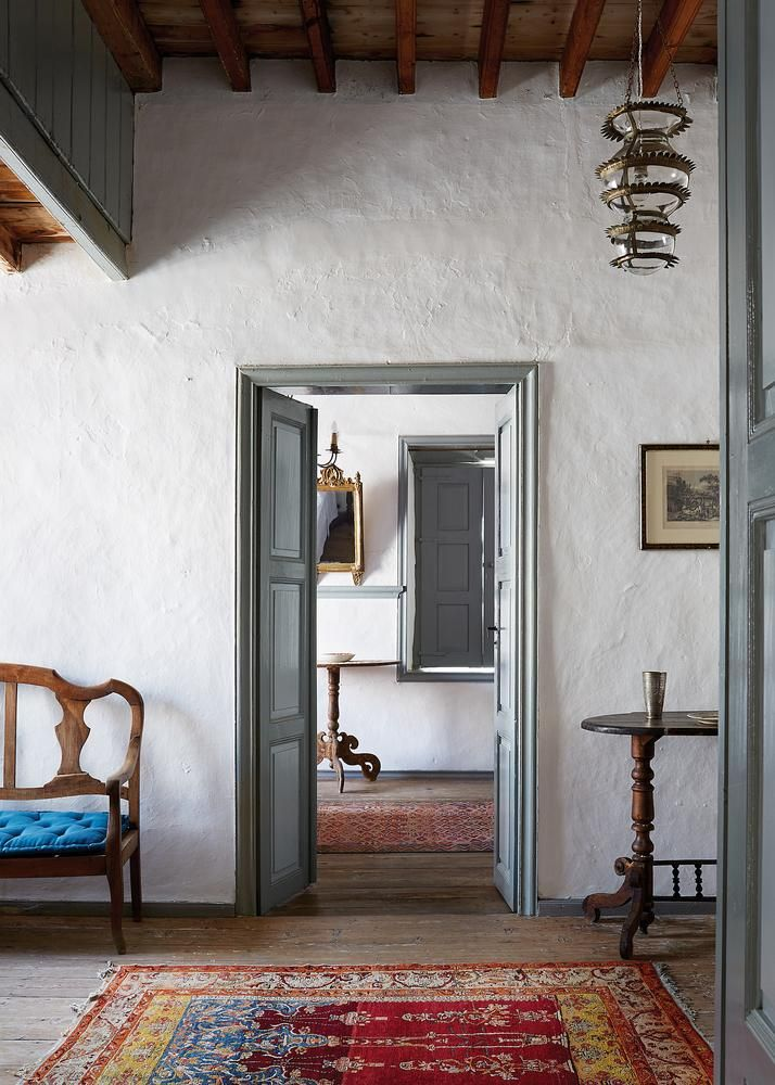 <strong>GRAND ENTRANCE</strong>   The first-floor hall of Stefania, featuring a gilded monastery lantern and a gold-leaf mirror from Lesbos.