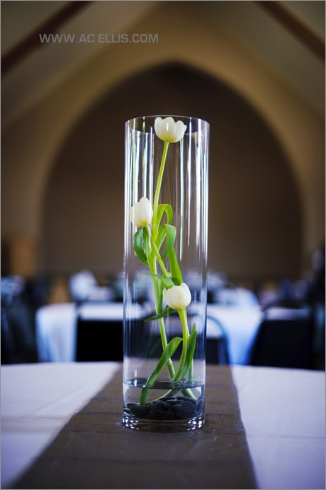 Yes. I've decided. Long vase with a tulip in water. Maybe 3 vases of various lengths, but it's simple and elegant. Basically my theme. Maybe a cream and olive green bow around the base of the vases to add in my colors.