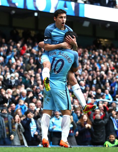 Sergio Aguero (R) and Jesus Navas (L) of Manchester City  celebrate their team's first goal during the Premier League match between Manchester City and Chelsea at Etihad Stadium on December 3, 2016 in Manchester, England.