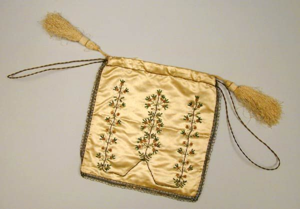 """Small white satin """"square"""" bag lined with white silk, and edged with gold lace and gold cord drawstrings with white silk tassels. Decorated on both sides with sprays of bead flowers in green and gold. c. 1800"""