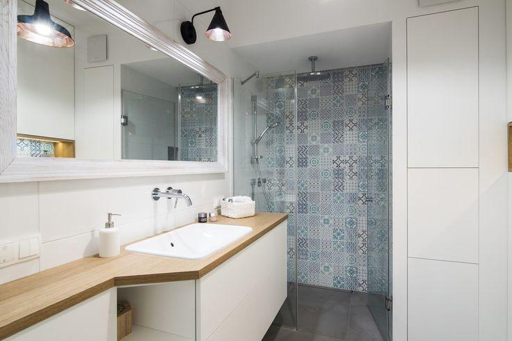 Aranżacja całkiem przestronnej łazienki w stylu skandynawskim, gdzie dominuje biel i drewno. Wzorzysta ściana w części...