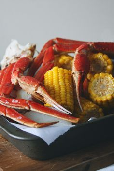 Snow crab legs get boiled in Old Bay seasoning with corn and potatoes and served with butter, bread, and brews