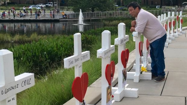 Jose Luis Morales holds onto a cross memorial for his friend, Eddie Sotomayor, a victim in the June 12 shooting rampage at Pulse nightclub in Orlando. Morales said at least two of five friends who died in Pulse were Puerto Ricans.