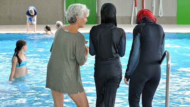Symbolbild: Zwei muslimische Mädchen stehen mit Burkinis bekleidet am Rand eines…