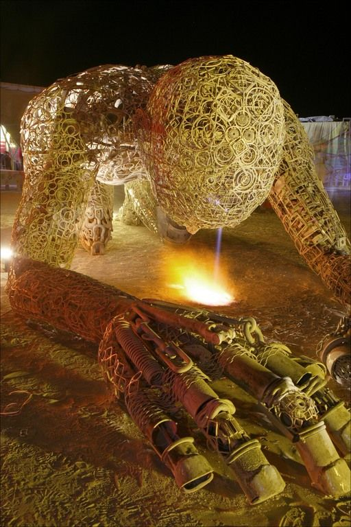 Sculpture pouring out fire at Center Camp at Burning Man  Have your own original Burning Man photos? Inspire the journey at trover.com! We're travel photo junkies.