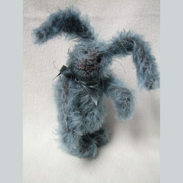 I'd like you to meet Eli, He is a 7.5 inch tall Blue and brown rabbit. He has been lovingly created from a gorgeous blue mohair that has a brown backing. He has black glass eyes with a face full of curly dark whiskers. Eli features wired ears that can be gently posed and had jointed arms, legs and head - so he can be posed in many different ways.Eli has been designed and completely hand made by Canadian artist Melanie Clark.