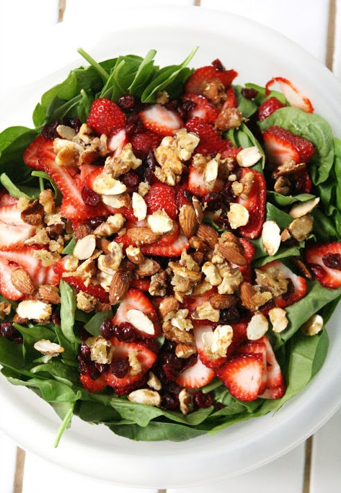 Spinach strawberry salad   Ingredients: -1 bag of ready-to-eat spinach -craisins -thinly sliced strawberries -sugar-coated almonds* -poppy seed dressing