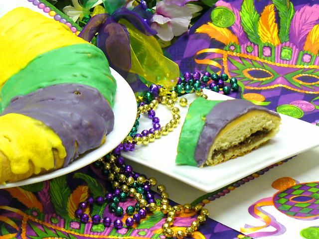 Fast and easy King Cake has a raisin, pecan, and cinnamon cream cheese filling. It is decorated with the traditional colored stripes for Mardi Gras.