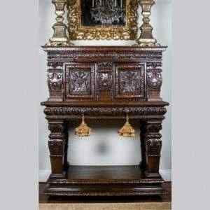 Italian walnut cabinet extensively carved with greco-roman motifs. comprising of two doors with carved satyr masks surrounded by acanthus leaves. the two gadrooned drawers above a pillared base standing on large bun feet.