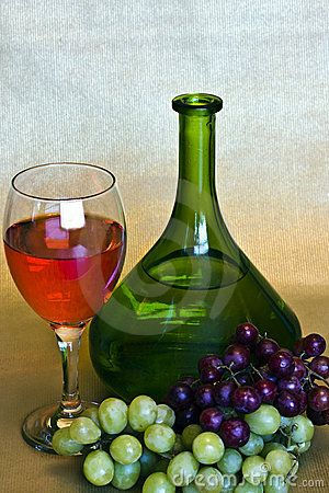 A still life of a bottle of  wine and a glass of  wine and two bunches of grapes