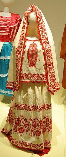 Traje típico de Colima que portan con más orgullo blusa y falda en tela blanca bordado con punto de cruz con hilo rojo y los bordes con ganchillo.