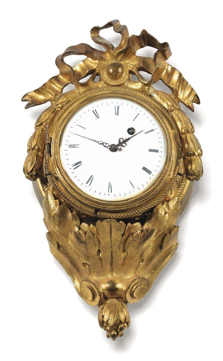 Porte-montre en bronze doré d'époque Louis XVI, le mouvement signé L.F. Benoist / A PARIS et numéroté N.2919 A GILT-BRONZE WATCH HOLDER, LOUIS XVI, THE WATCH MOVEMENT SIGNED L.F. BENOIST / A PARIS AND NUMBERED N.2919 sommé d'un noeud de ruban et de guirlandes de laurier, terminé par un cul-de-lampe feuillagé Haut. 15 cm Height 6 in