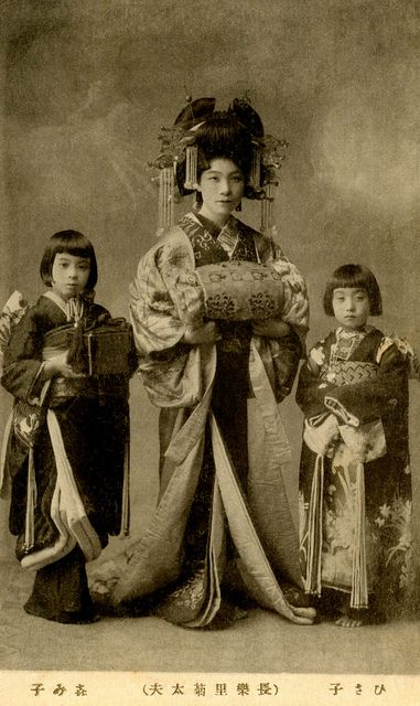 Satogiku-dayuu 1910s | It was customary for a tayuu (Japanese courtesan) to have two kamuro (child attendants) of about the same age and size, with names that matched in concept and sound, taking their cue from the name of their ane-jōro (elder sister courtesan).