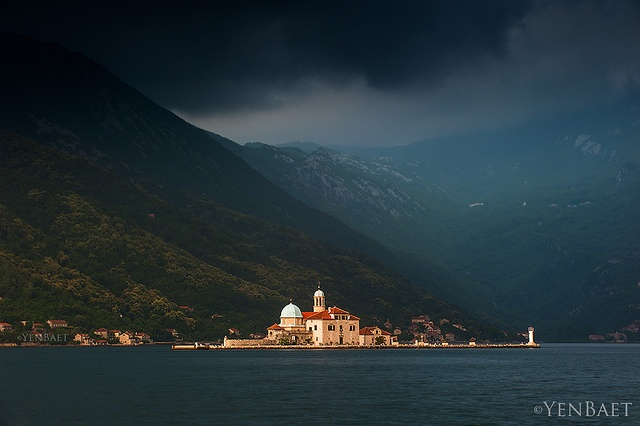 Perast, Montenegro - Dark Clouds over Our Lady of the Rock - Photo © www.YenBaet.com. Our Lady of the Rock is one of the two islets off the coast of Perast in Bay of Kotor. A local legend says the islet was made by sailors over the centuries. After finding the icon of Madonna and Child on the rock in the sea on July 22, 1452, they all made a solemn oath to build an island. So they all threw a rock in the bay after they have returned from each voyage. Over time, these rocks formed an island.