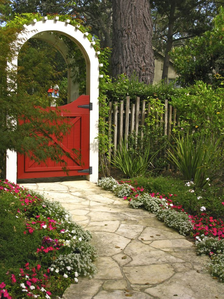 Red and white impatiens frame the walkway leading up to an arbor garden gate in the same colors. Lovely.