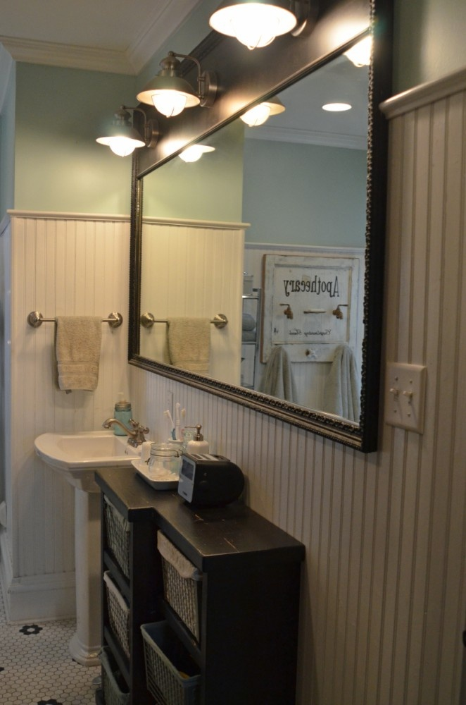mirror framed with antique plaster molding topped with three vintage style sconce lights designed