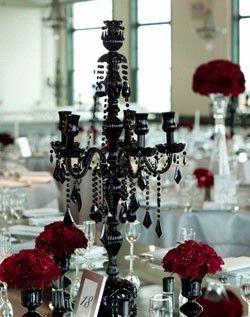 Incredible wedding centerpieces; beautiful black gothic chandelier surrounded by red flowers on white linens.