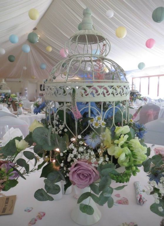 Beautiful birdcage wedding centrepiece in pastels