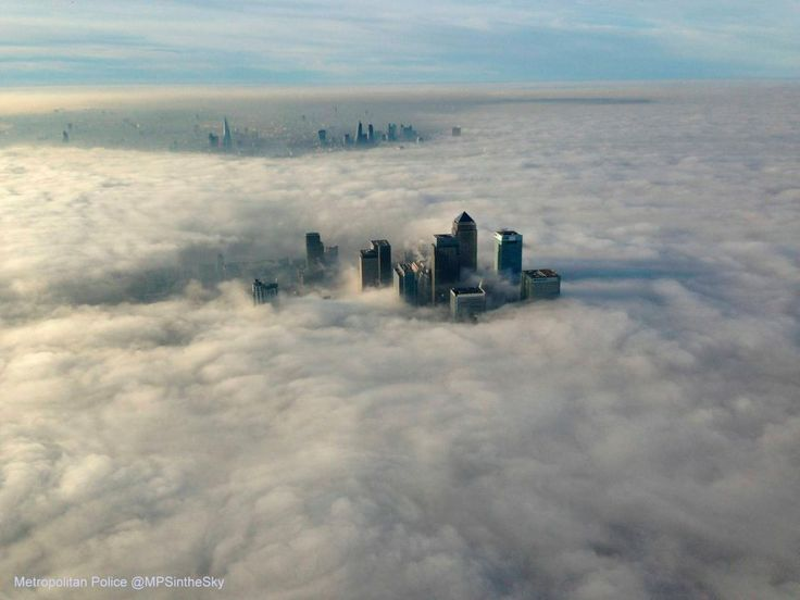 LONDYN - Canary Wharf - biznesowa dzielnica Londynu - została niemal zupełnie zasłonięta przez gęste chmury. Zdjęcie zostało wykonane z pokładu policyjnego helikoptera