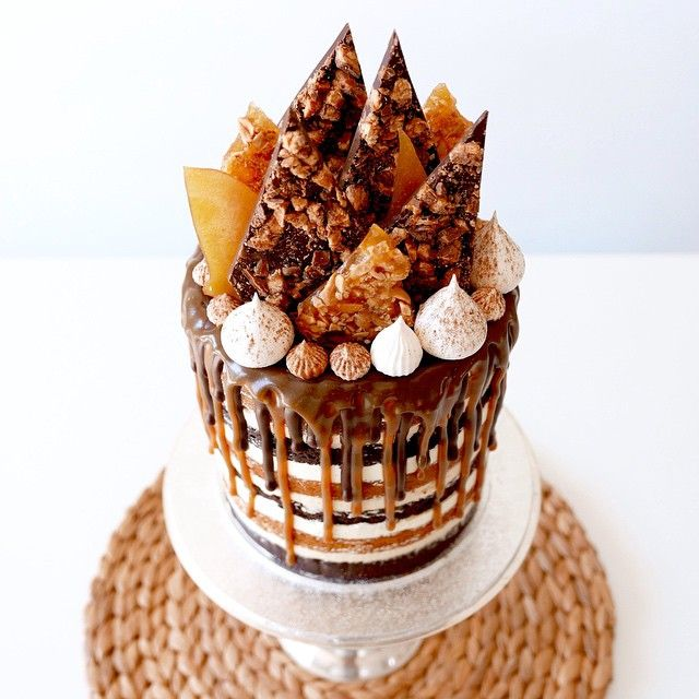 chocolate and caramel snickers mud cakes layered between peanut butter and vanilla bean buttercreams, drizzled with dark chocolate and salted caramel, topped off with meringues, peanut brittle, toffee and chocolate snickers shards