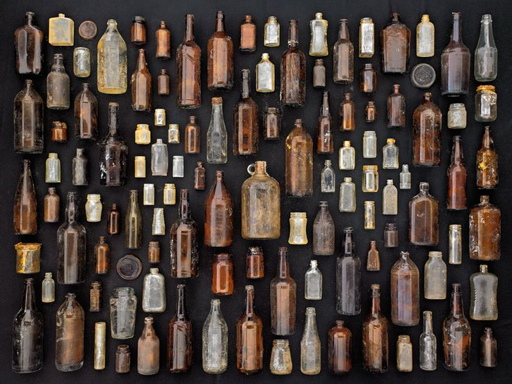 """SUBMISSION: Brown and clear glass bottles on black background.  Found objects collected on Floyd Bennett Field, Brooklyn, New York. From the series of photographs """"Found in Nature"""" by Barry Rosenthal."""