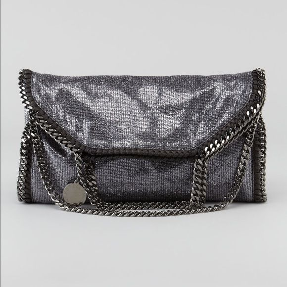 """Stella McCartney  Fold-Over Falabella Tote Bag The Falabella bag is a Stella McCartney favorite for its edgy design and vegan-friendly construction. Metallic vegan-friendly faux leather. Signature whipstitching and silvertone curb-chain trim, top handles with 5"""" drop, and removable strap. """"Stella McCartney"""" charm hangs from top handles. Slouchy, yet structured body may be folded over and carried like a clutch. Dipped top with magnetic-snap closure. Fabric lining; inside zip pocket. 14""""H x…"""
