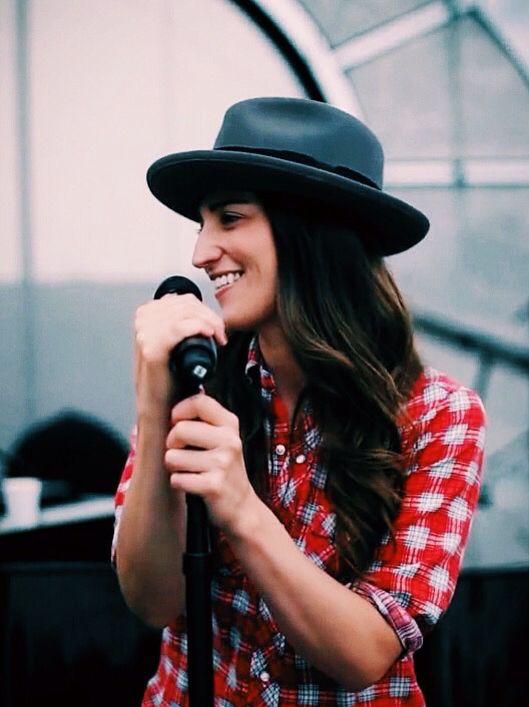 "Sara Bareilles, outfit bueno con blusa de botones tipo ""cuadros"" rosa cu detalles blancos mas un sombrero gris"
