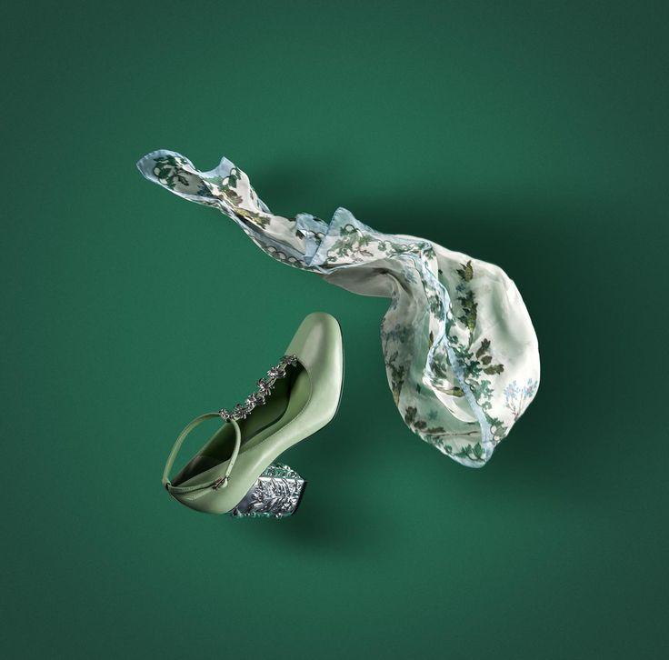 Романтичные туфли мэри-джейн из кожи зеленого цвета. Тонкие ремешки украшены металлической фурнитурой, напоминающей листики, каблук серебряного цвета дополнен фигурной резкой.