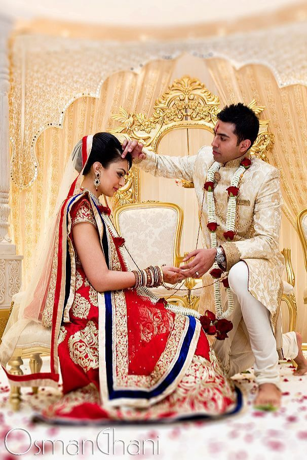 The groom applies the red sindoor or kumkum on the hair-arting / forhead of his bride, as a symbol of their marriage.-Indian wedding