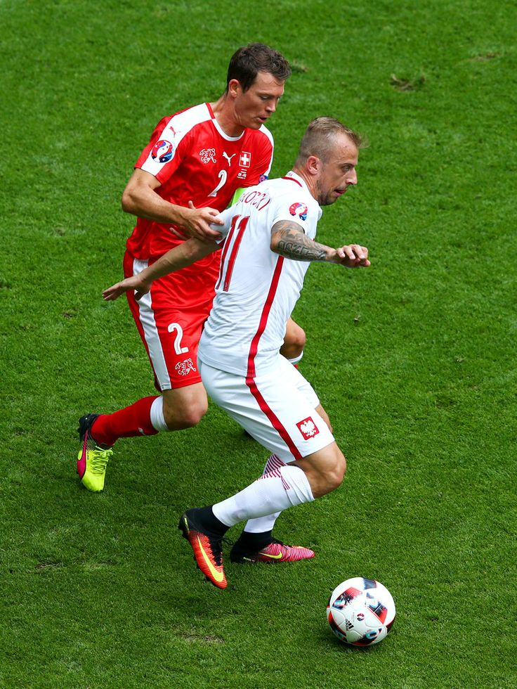 Kamil Grosicki of Poland controls the ball under pressure of Stephan Lichtsteiner of Switzerland during the UEFA EURO 2016 round of 16 match between Switzerland and Poland at Stade Geoffroy-Guichard on June 25, 2016 in Saint-Etienne, France.