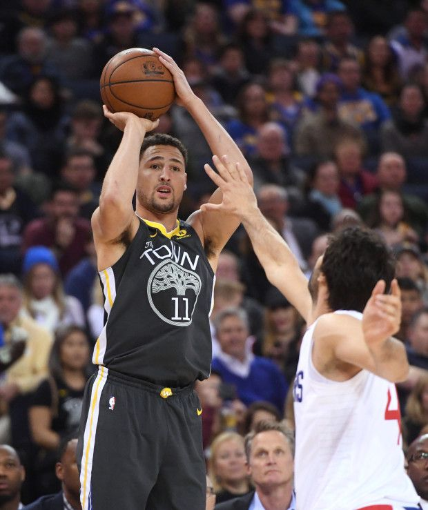 Golden State Warriors' Klay Thompson (11) makes a three-point basket as Los Angeles Clippers' Milos Teodosic (4) tries to block in the first period of their NBA game at Oracle Arena in Oakland, Calif., on Thursday, Feb. 22, 2018. Thompson's basket was his 10,000th career point. (Doug Duran/Bay Area News Group)