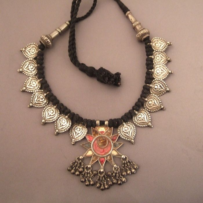 A pretty old necklace coming from the North of India which combines nicely colored molten glass, silver grelots and silver floral motives