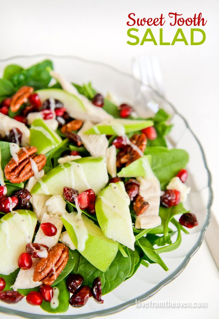 Sweet Tooth Salad Recipe ~ Baby spinach, dried cranberries, pomegranate seeds, sliced apples, feta cheese, candied pecans, grilled chicken and a drizzle of poppy seed dressing.