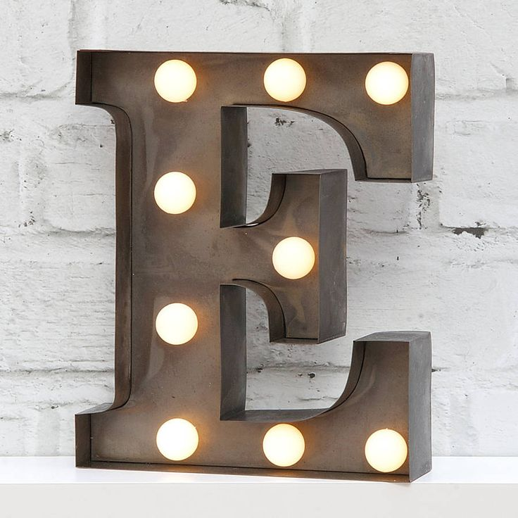"9"" carnival light LED battery powered metal letter light.Available in industrial silver finish. Please note each shape is finished by hand and may vary from photo. For indoor use only.Illuminated letters make a great personalised gift. These 9"" lights are a smaller cute version of our larger lights. Great freestanding on bookcase or shelf with hanger at back of letter for wall mounting. Battery powered LED lights give a soft glow. LED Lights have life-time of up to 30,000 hours. Battery ..."