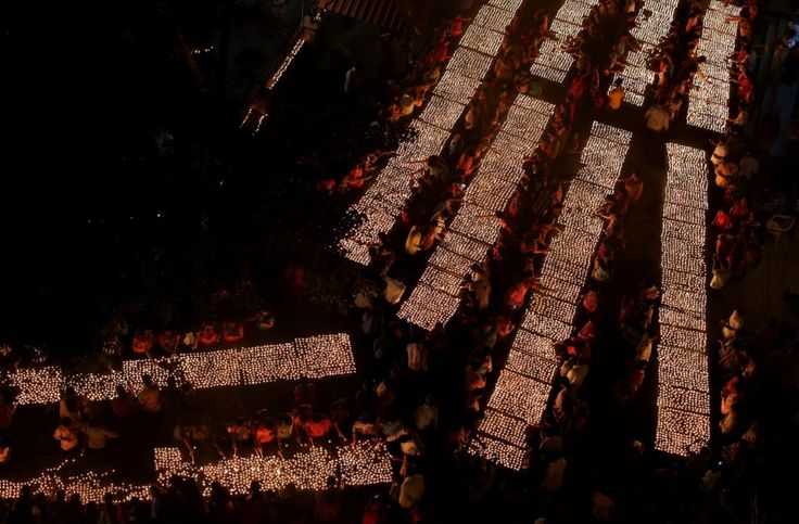 Hindu devotees light earthen lamps at a temple on Karthik Purnima in Hyderabad, India, Wednesday, Nov. 25, 2015. Karthik Purnima is celebrated on the full moon day of the Hindu calendar month of Karthik and considered very auspicious by Hindus. (AP Photo/Mahesh Kumar A.)