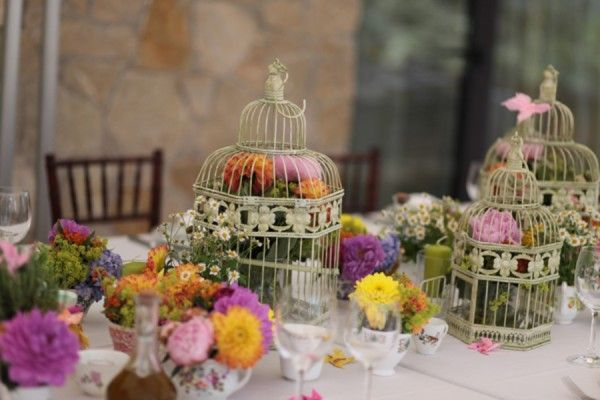 Bird cages and tea cups filled with flowers. So colorful.