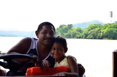 Father and daughter working Lake Gatun in the Panama Canal. He hires out his boat and she gets to ride around the lake's many islands on weekends!