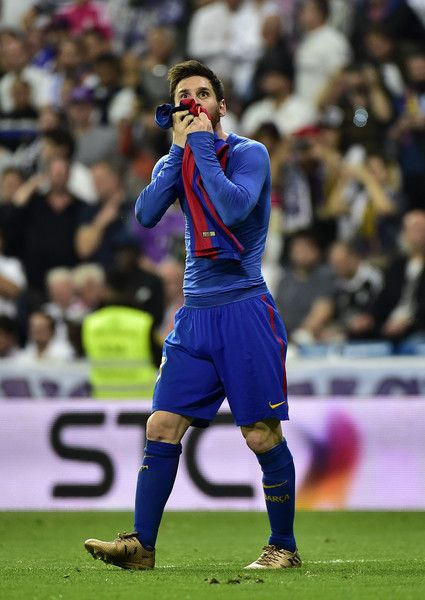 Barcelona's Argentinian forward Lionel Messi kisses his jersey after brandishing it to celebrate his goal during the Spanish league Clasico football match Real Madrid CF vs FC Barcelona at the Santiago Bernabeu stadium in Madrid on April 23, 2017..Barcelona won 3-2. / AFP PHOTO / GERARD JULIEN