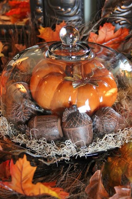 Cake platter filled with moss, wooden acorns, and a big pumpkin
