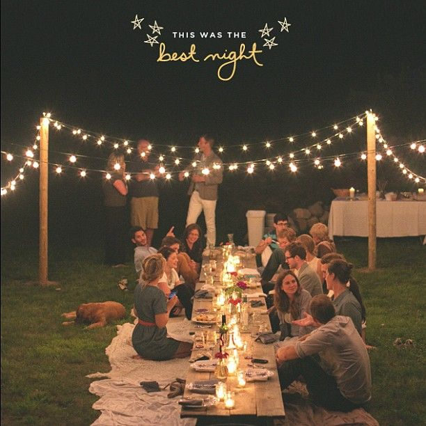Long tables with blanket seating on either side at an outdoor party/dinner- rehearsal dinner