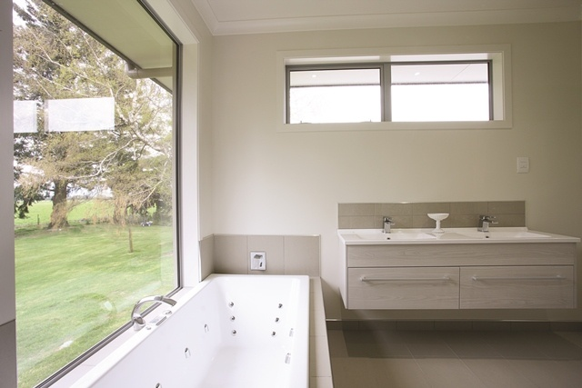 A feature window in the master bedroom ensuite lets the homeowners enjoy winter snowfalls from the tub.