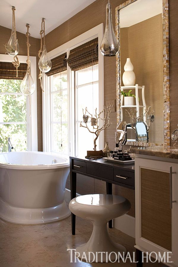 In the bathroom, a freestanding tub, a grass cloth wall covering, and hanging terrariums create a study in serenity. - Photo: John Bessler / Design: Heather Garrett